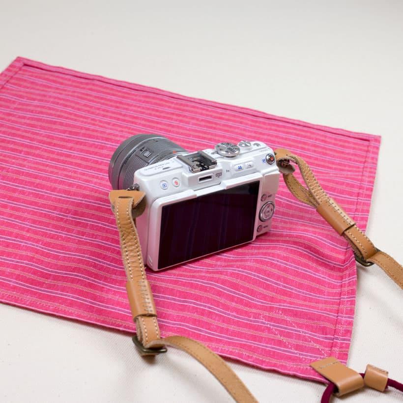 クロスの裏面が表となるように置き、クロスのコードがカメラの背面側にして、カメラを上にのせる。